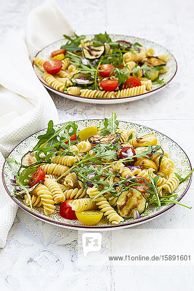 Two plates of vegetarian pasta salad with grilled zucchini  tomatoes  arugula  red onions and balsamic vinegar
