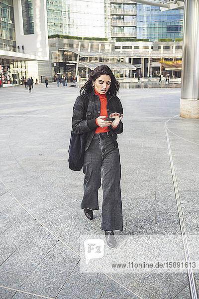 Schöne Frau mit Smartphone geht auf einem Platz