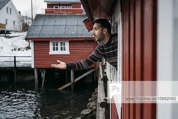 Tourist  der sich aus dem Fenster einer Hütte lehnt  Lofoten  Norwegen