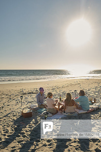 Ältere Freunde im Urlaub  die an sonnigen Tagen ein Picknick am Strand genießen. Riviera Nayarit  Mexiko