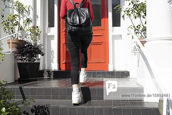Junge Frau kommt an der Haustür an Junge Frau kommt an der Haustür an