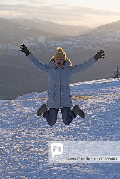 Woman jumping in winter on sunset.