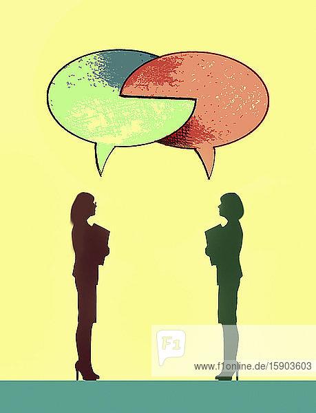Two businesswomen with interlocking speech bubbles