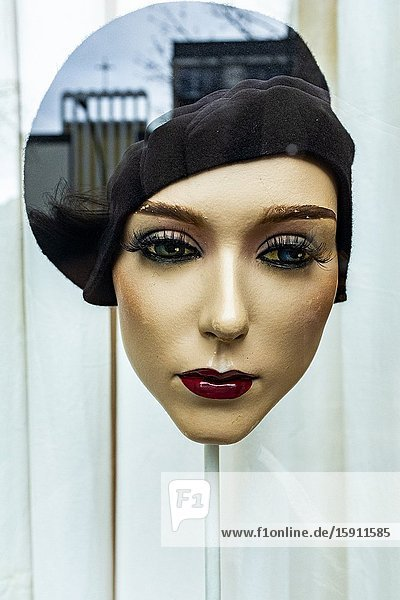 Berlin  Germany. An Artificual Mannequin Head with head on display inside a shop's and fashion store window  reflecting a church inside her head.