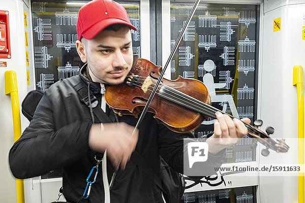 Berlin  Germany. Street musician performing his music inside an U-Bahn train to earn a bit of coin and cash.