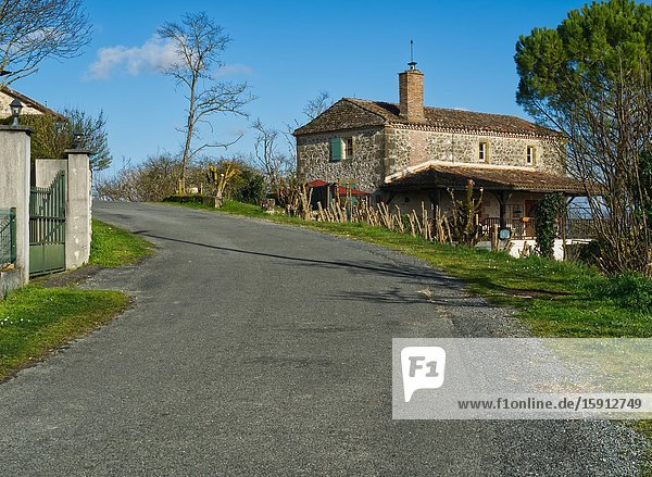 Stone house and empty road in the countryside near Tourtres  Lot-et-Garonne Department  Nouvelle Aquitaine  France.