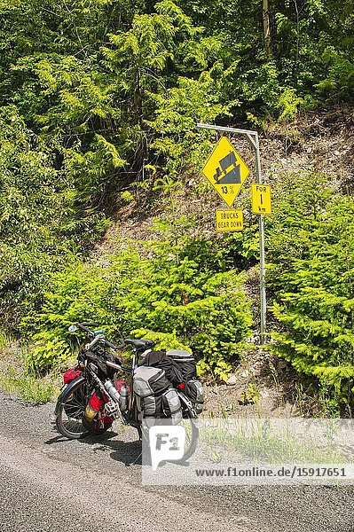 Loaded bicycle beside steep downhill warning sigh  Duffy Lake Road  Cayoosh Mountain Range  British Columbia  Canada.