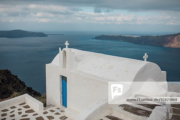 Views from Imerovigli  with a church  the Aegean Sea and Oia in Santorini  Greece.