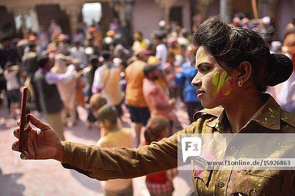India  Uttar Pradesh  Holi festival  Colour and spring festival celebrating the love between Krishna and Radha . Policewoman making a selfie.