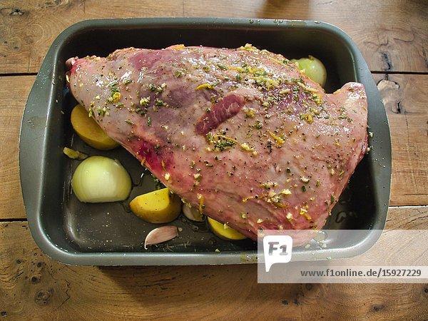 Leg of lamb with potatoes and onions ready for roasting  Lauzun  Lot-et-Garonne Department  Nouvelle Aquitaine  France.