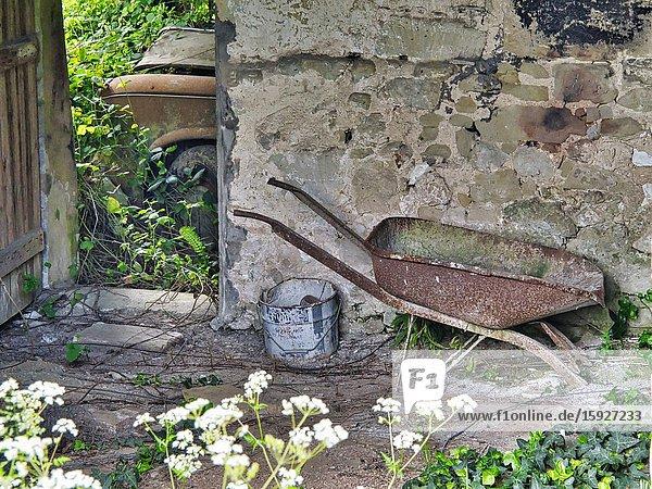 Abandoned wheelbarrow and rusty Peugeot 403 car  Lauzun  Lot-et-Garonne Department  Nouvelle Aquitaine  France.