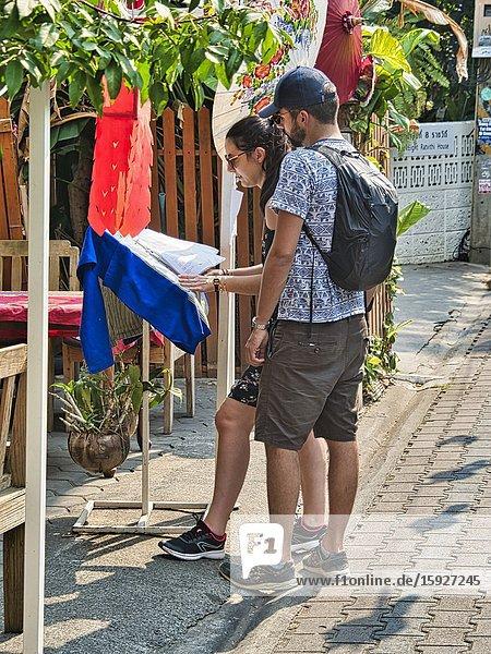 Couple reading a menu outside a restaurant  Rathvithi Soi 1  Chiang Mai  Thailand.