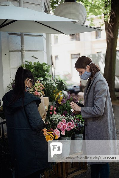Woman with mask buying flowers.