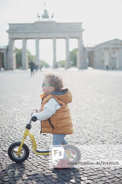 Little boy 2-3 Years old with bicycle and mask in front of Brandenburg gate in Berlin.