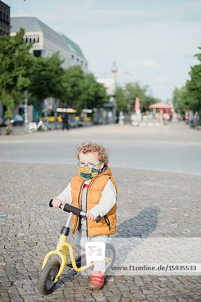 Little boy 2-3 years old with mask and bicycle in Berlin.