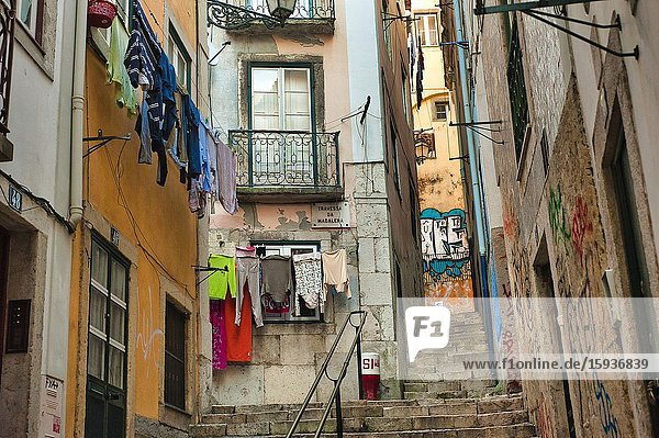 Narrow streets with laundry hanging to dry and graffiti in Alfama neighbourhood  Lisbon  Portugal.