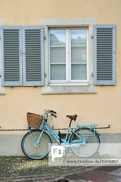 Blue bicycle withwicker basket parked under shuttered window  Freiburg  Baden-Wurttemberg  Germany.