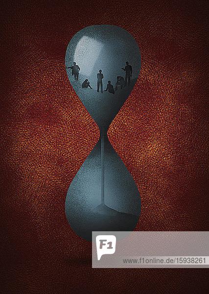 Zeit läuft ab für Menschen in einer Sanduhr