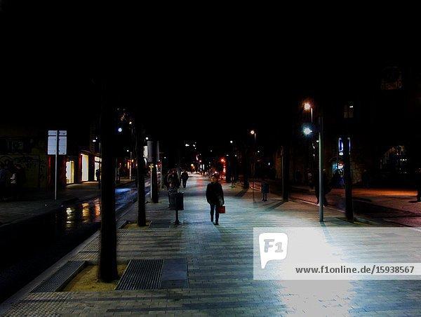 Pedestrians Walking Along Street with Flashing Lights at Night