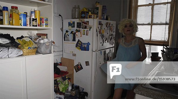 Woman in Blonde Wig and Blue Nightgown Dancing in Kitchen