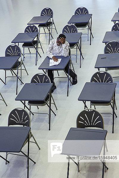 Engagierter High-School-Schüler nimmt Prüfung am Schreibtisch im Klassenzimmer ab