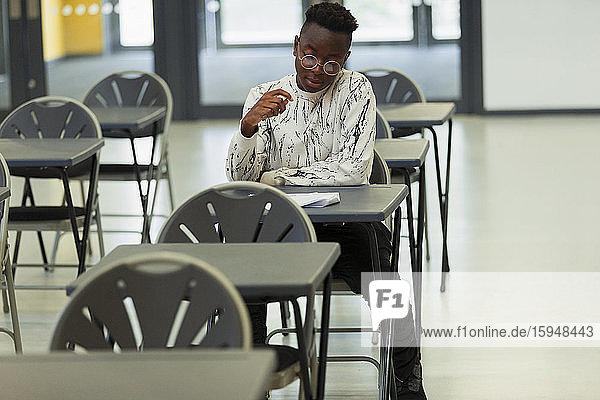 High-School-Schüler nimmt Prüfung am Schreibtisch im Klassenzimmer ab