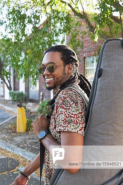 Porträt eines lächelnden männlichen Musikers mit Gitarre auf der Straße