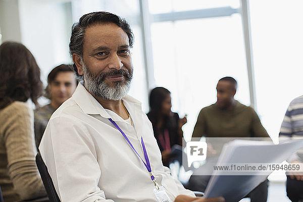 Porträt eines selbstbewussten Geschäftsmannes mit Papierkram in Bürobesprechung
