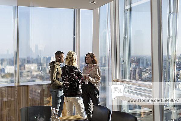 Geschäftsleute im Gespräch am sonnigen Bürofenster des Hochhauses