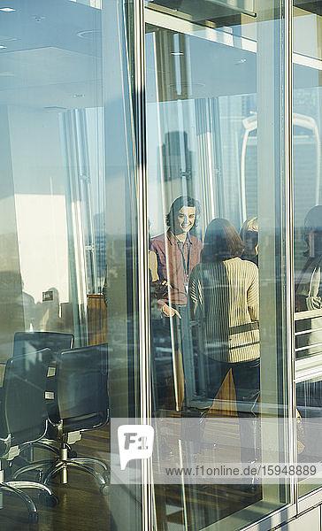 Geschäftsleute im Gespräch am sonnigen Bürofenster