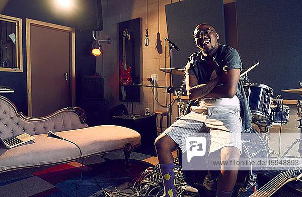 Porträt eines glücklichen männlichen Musikers  der am Schlagzeug im Aufnahmestudio sitzt