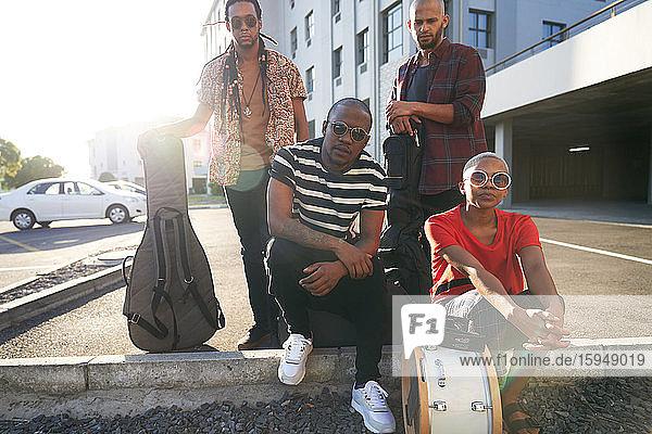 Porträt selbstbewusster cooler Musiker auf sonnigem Parkplatz