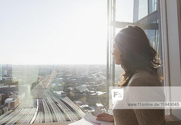 Nachdenkliche Geschäftsfrau am sonnigen Fenster mit Blick auf die Stadt