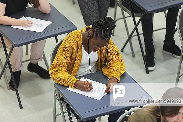 Fokussierte High-School-Schülerin nimmt Prüfung am Schreibtisch im Klassenzimmer ab