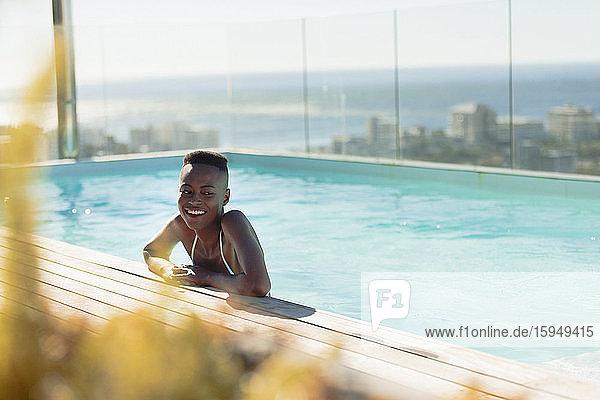 Glückliche junge Frau in sonnigem  luxuriösem Schwimmbad
