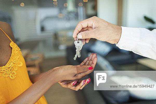 Nahaufnahme eines Mannes  der einer Frau einen Hausschlüssel gibt