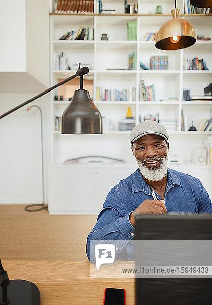 Porträt eines selbstbewussten  lächelnden Mannes  der im Home Office arbeitet