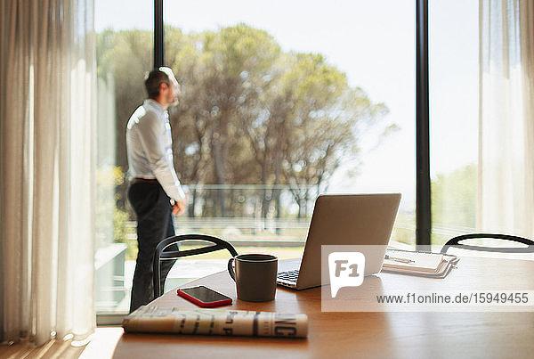 Geschäftsmann macht eine Pause von der Arbeit zu Hause und steht an sonniger Terrassentür
