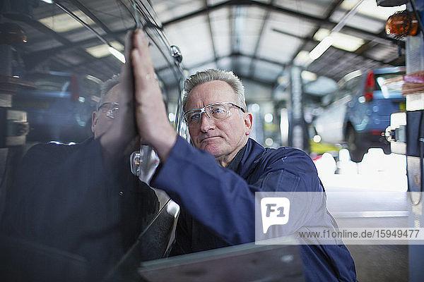 Männlicher Mechaniker untersucht Auto in Autowerkstatt