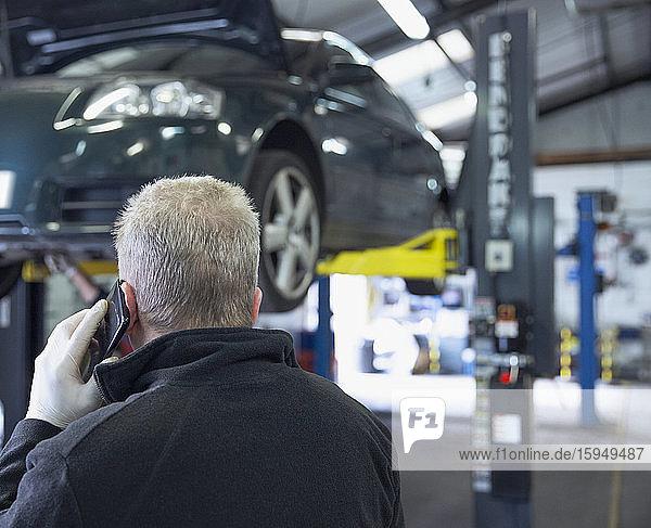 Männlicher Mechaniker spricht mit Smartphone in Autowerkstatt