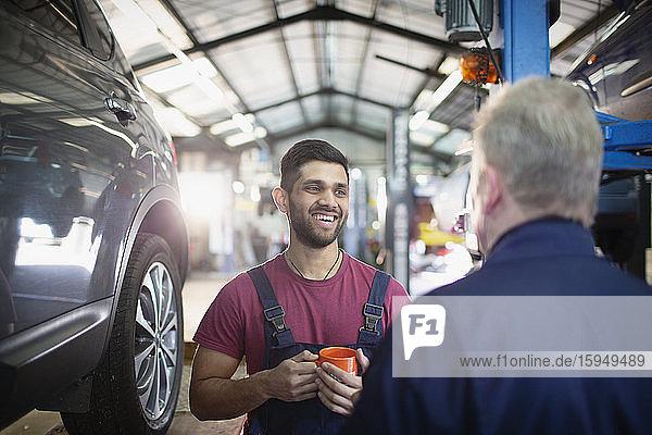 Lächelnde  fröhliche männliche Mechaniker  die sich unterhalten und Kaffee in der Autowerkstatt trinken