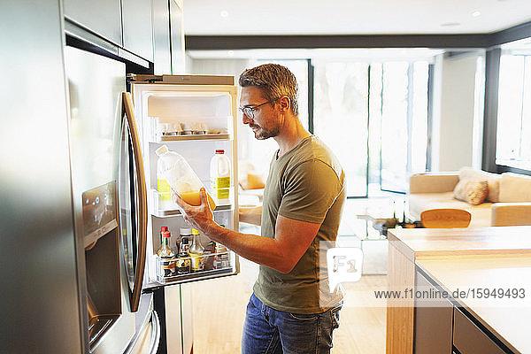 Mann hält Orangensaft am offenen Kühlschrank in der Küche