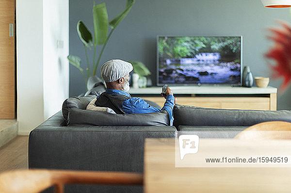Mann sieht auf Wohnzimmersofa fern