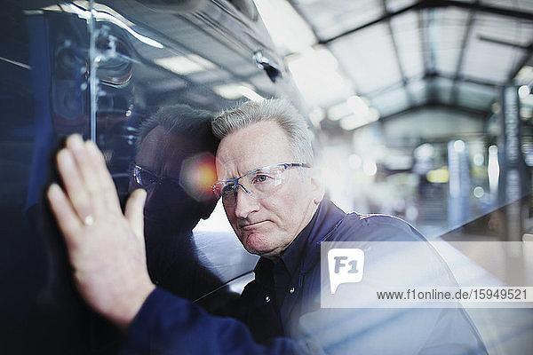 Fokussierter männlicher Mechaniker untersucht Auto in Autowerkstatt