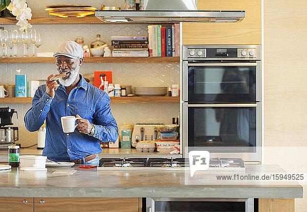 Mann genießt Toast und Kaffeefrühstück in moderner Küche