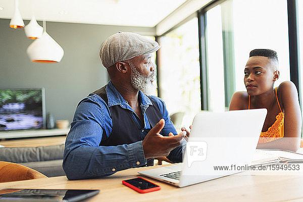 Vater und Tochter unterhalten sich  arbeiten am Laptop