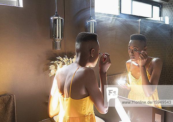 Junge Frau trägt Wimperntusche im sonnigen Badezimmerspiegel auf