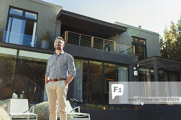 Lächelnder  selbstbewusster Mann auf sonniger  luxuriöser Terrasse