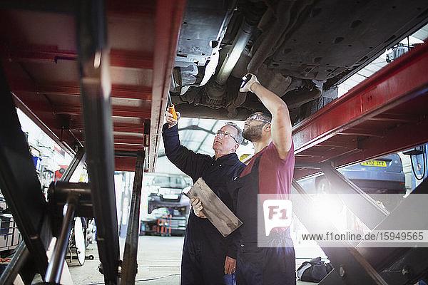 Männliche Mechaniker mit Taschenlampe arbeiten unter dem Auto in einer Autowerkstatt