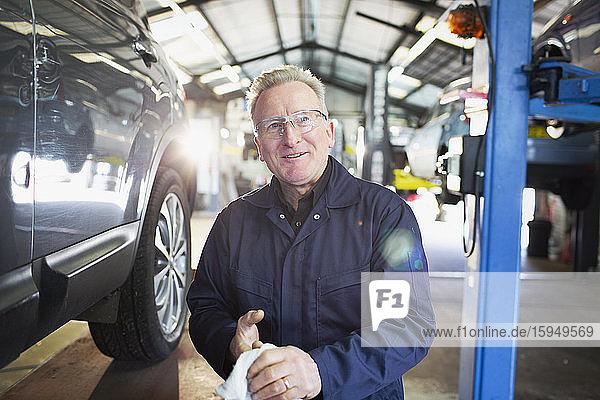Porträt eines selbstbewussten Mechanikers beim Händewischen in einer Autowerkstatt